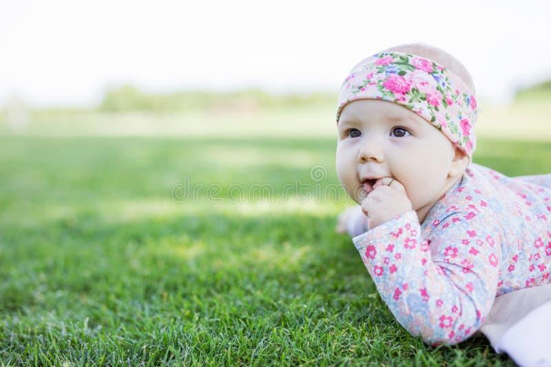 Gulligt behandla som ett barn flickan som ser upp, medan ligga ner på gräs, parkerar in arkivbilder