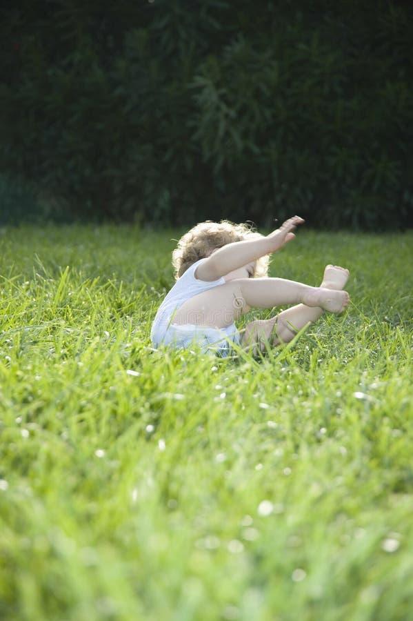 Gulligt behandla som ett barn flickan som rasar på gräs royaltyfri fotografi