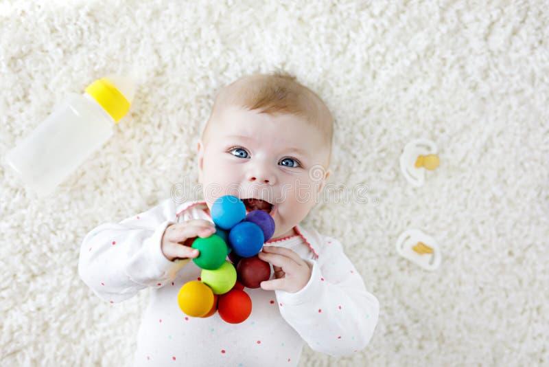 Gulligt behandla som ett barn flickan som spelar med den färgrika träpladderleksaken, sjukvårdflaskan och attrappen arkivbilder