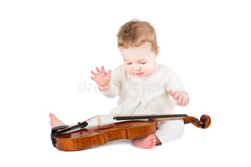 Gulligt behandla som ett barn flickan som spelar med en fiol arkivbilder