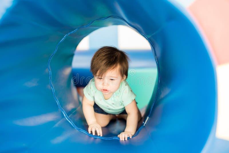 Gulligt behandla som ett barn flickan som undersöker en tunnel arkivbild