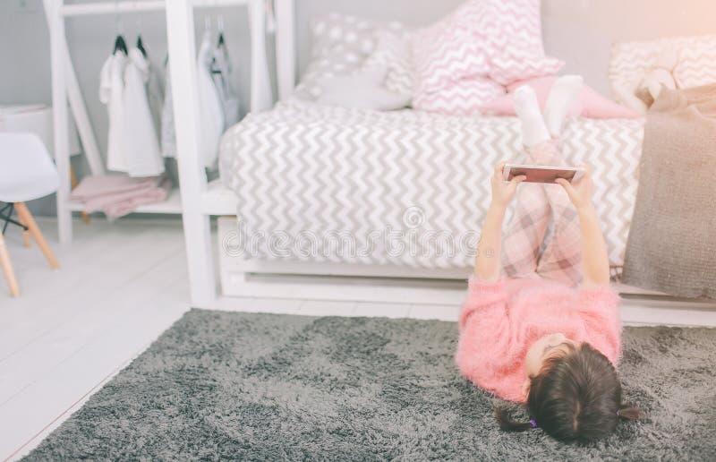 Gulligt behandla som ett barn flickan som spelar en smart telefon, har Smartphone negativ inverkan på dina utveckling och mentala arkivbilder