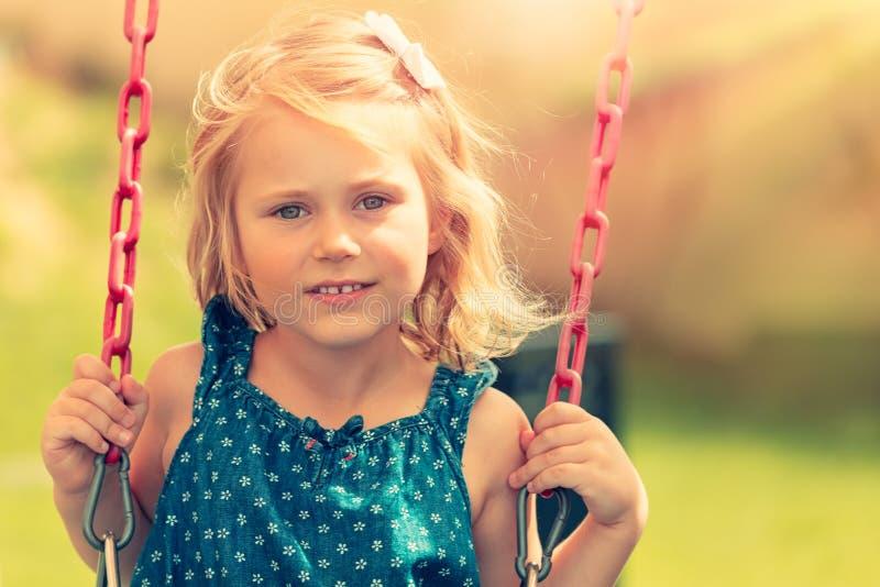 Gulligt behandla som ett barn flickan som svänger på gunga royaltyfri fotografi