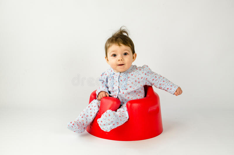 Gulligt behandla som ett barn flickasammanträde i en plast- plats arkivfoton