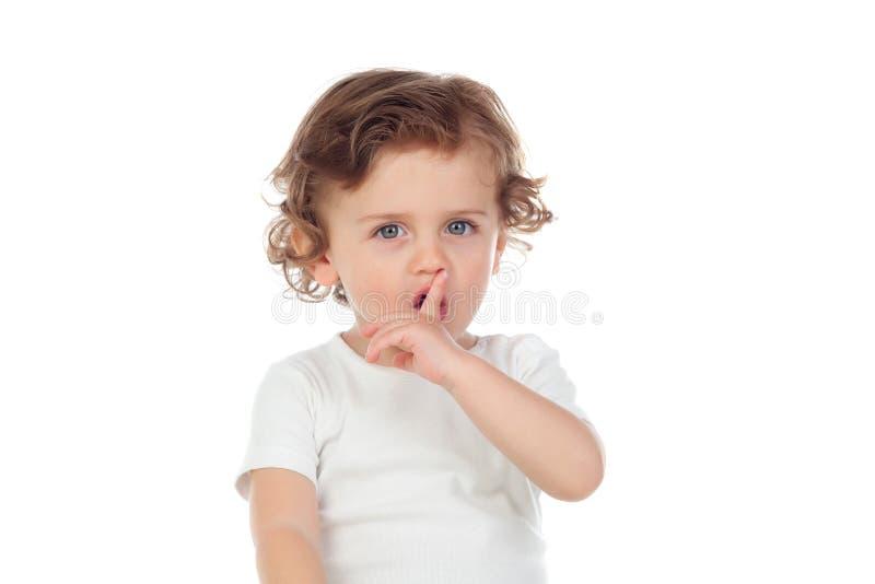 Gulligt behandla som ett barn har satt pekfingret till kanter som tecken av tystnad arkivfoto