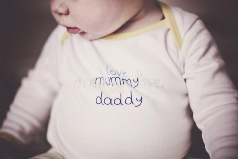 Gulligt behandla som ett barn i ljusa kläder med ord`en som jag älskar mamma- och pappa`, Efterföljd av filmkorn arkivfoto