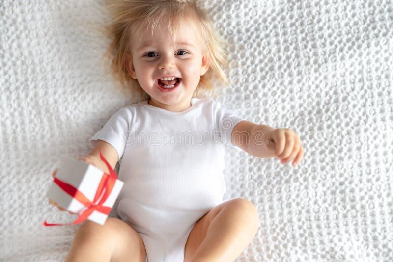Gulligt behandla som ett barn i vita Bodie Laughing på vit bakgrund Begrepp för barn` s royaltyfri foto
