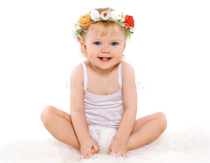 Gulligt behandla som ett barn lilla flickan med den blom- kransen på hans huvud fotografering för bildbyråer