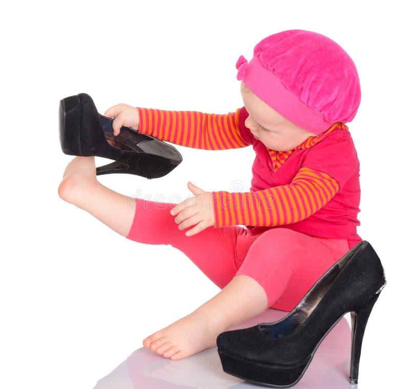 Gulligt behandla som ett barn lite flickan som är pröva på som henne, skor modern på vitbaksida royaltyfri foto