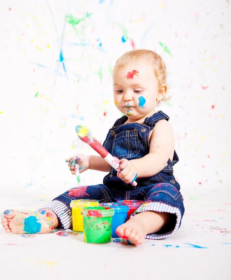 Gulligt behandla som ett barn little målningssplatterfärger arkivfoto
