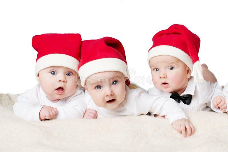Gulligt behandla som ett barn med santa hattar arkivfoton