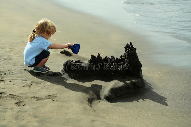 Gulligt behandla som ett barn pojkebyggandesandslotten på havsstranden royaltyfri fotografi