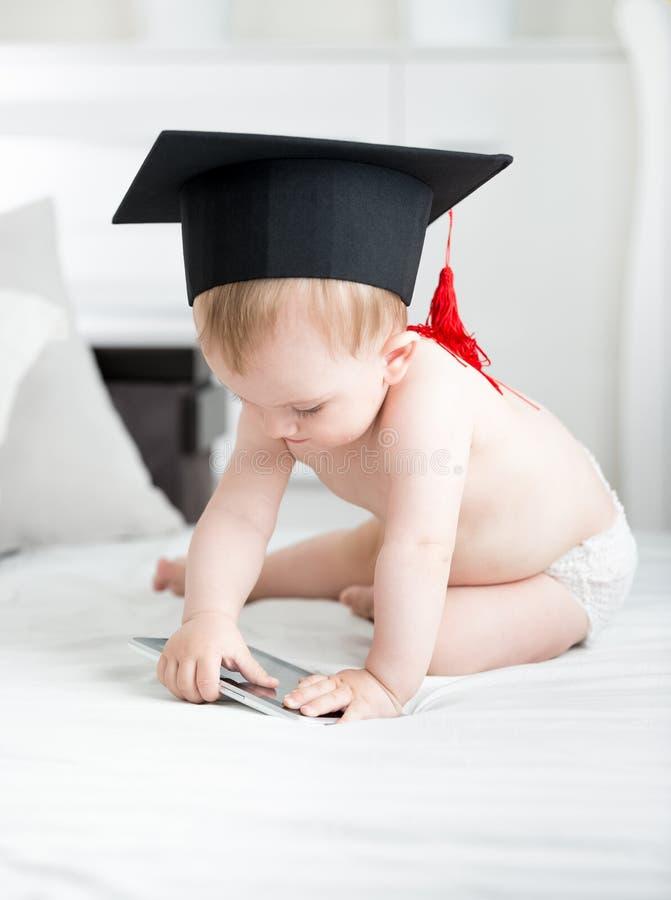 Gulligt behandla som ett barn pojken i avläggande av examenlocksammanträde på säng med den digitala minnestavlan Begrepp av smart arkivbild