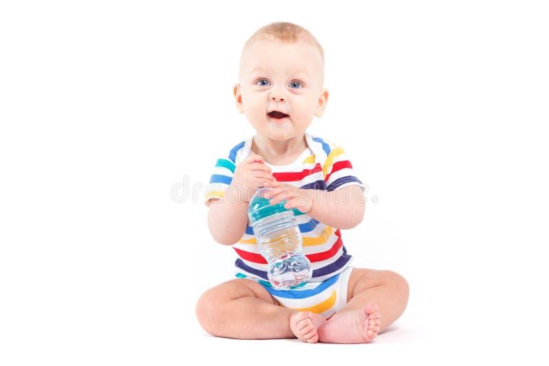 Gulligt behandla som ett barn pojken i färgrik skjorta med vatten arkivfoton