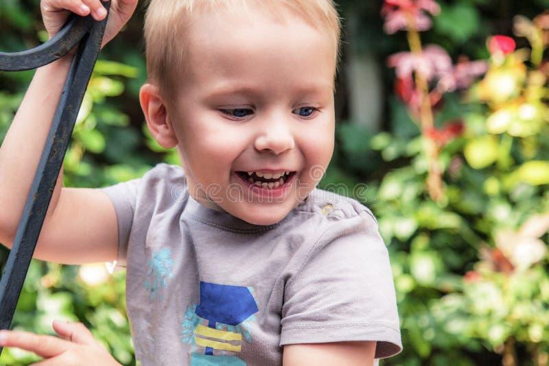 Gulligt behandla som ett barn pojken som ler grön blommabakgrund för utomhus- ot arkivfoto
