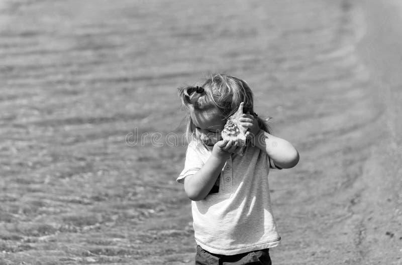 Gulligt behandla som ett barn pojken som lyssnar till snäckskalet på havsstranden arkivbild