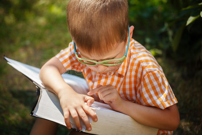 Gulligt behandla som ett barn pojken med exponeringsglas som läser boken i sommardag Utomhus tillbaka till skolabegreppet arkivfoto