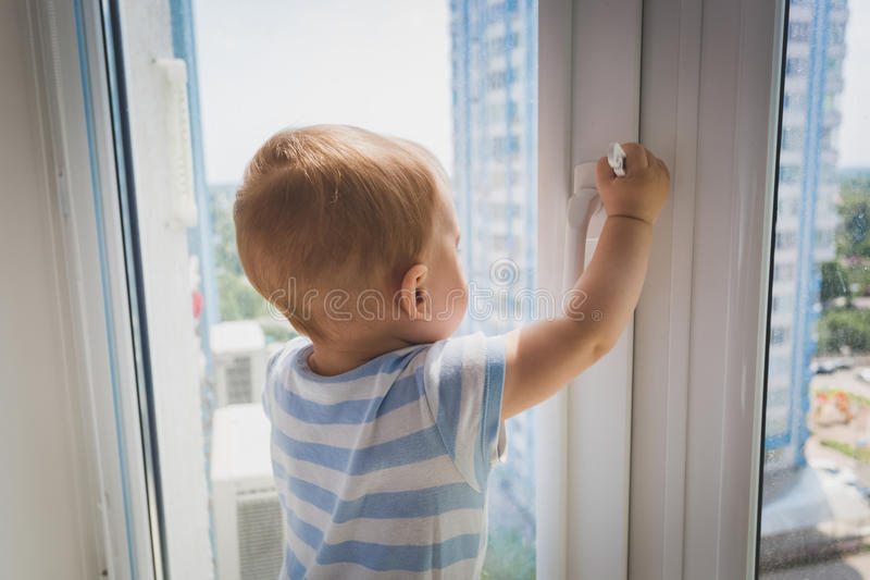 Gulligt behandla som ett barn pojken som drar vid fönsterhandtaget Begrepp av barnet in arkivfoton