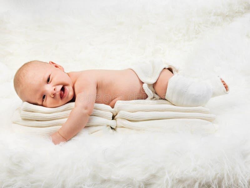 Gulligt behandla som ett barn pojken som kopplar av på bunt av handdukar royaltyfri fotografi