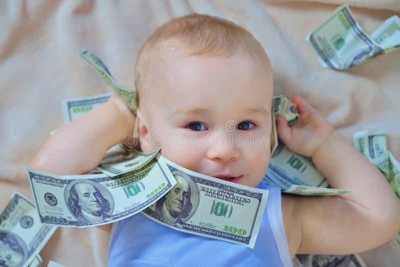 Gulligt behandla som ett barn pojken som spelar med pengar, oss kontanta dollar royaltyfria bilder