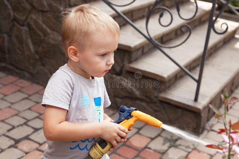 Gulligt behandla som ett barn pojkevatten blommorna på bakgården, moderassistent arkivfoto