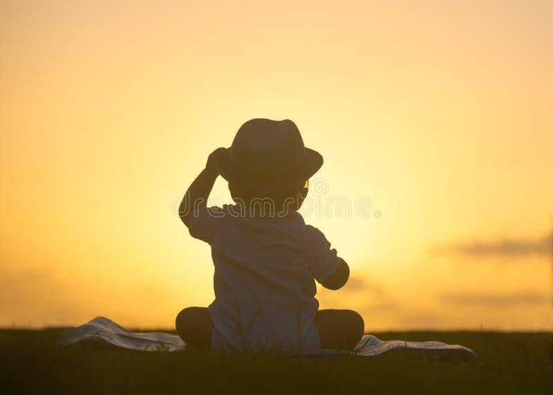 Gulligt behandla som ett barn solnedgångkonturståenden royaltyfria foton