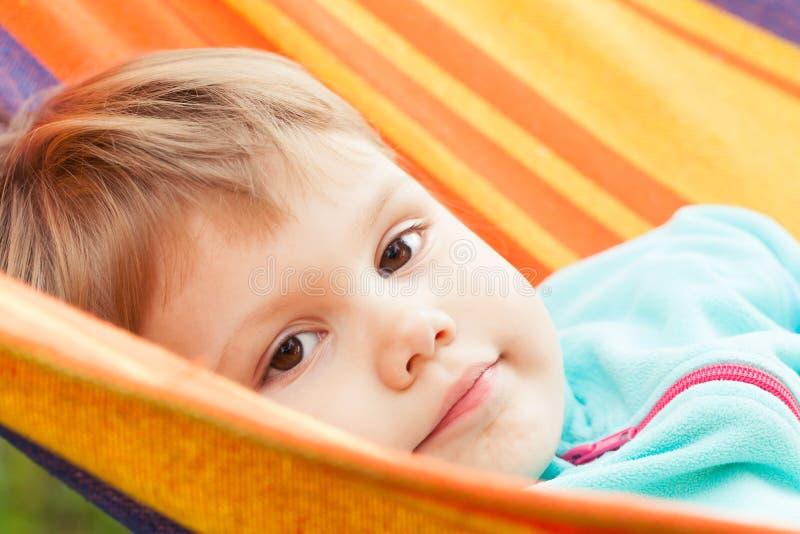 Gulligt blont behandla som ett barn flickan som ligger i randig hängmatta royaltyfri foto