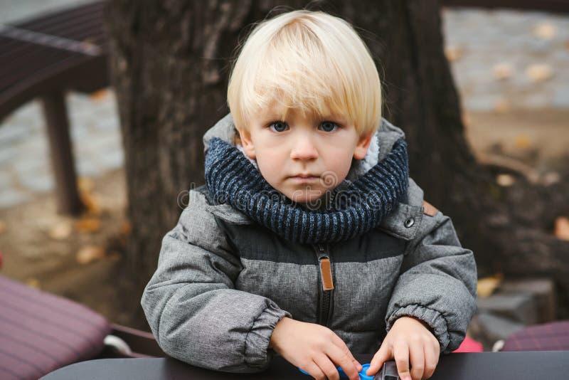 Gulligt blont behandla som ett barn pojken som spelar med leksaker utomhus Litet barnpojke med blåa ögon och blont hår Barnet i v royaltyfri bild