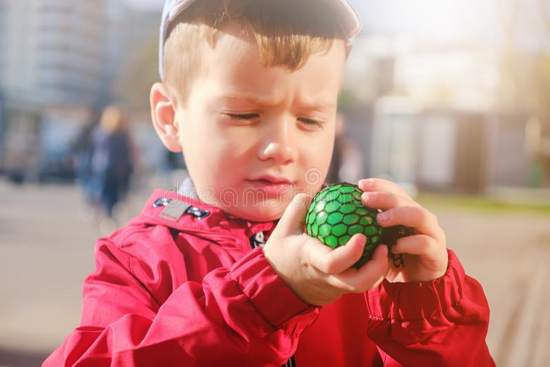 Gulligt caucasian barn som spelar handen - den gjorda leksaken kallade slam arkivbilder