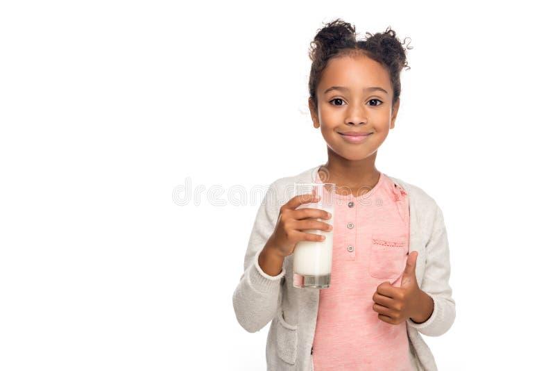gulligt dricka för afrikansk amerikanbarn mjölkar och uppvisning av tummen upp arkivfoto