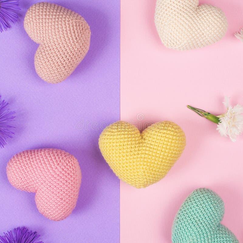 Gulligt färgrikt stilfullt modellfoto med små hjärtor och blommor Pastell färgade virkade hjärtor på rosa och lila pappers- backg arkivfoton