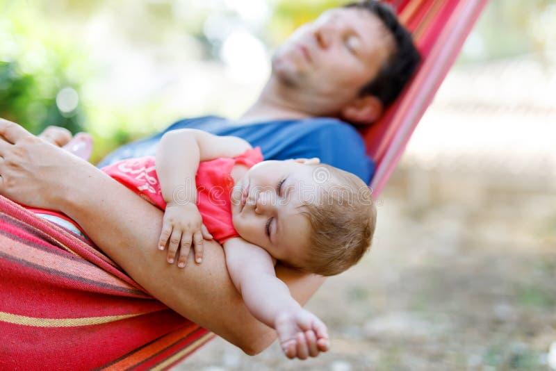 Gulligt förtjusande behandla som ett barn flickan av 6 fridsamma månader och hennes sova för fader i hängmatta i utomhus- trädgår royaltyfri fotografi