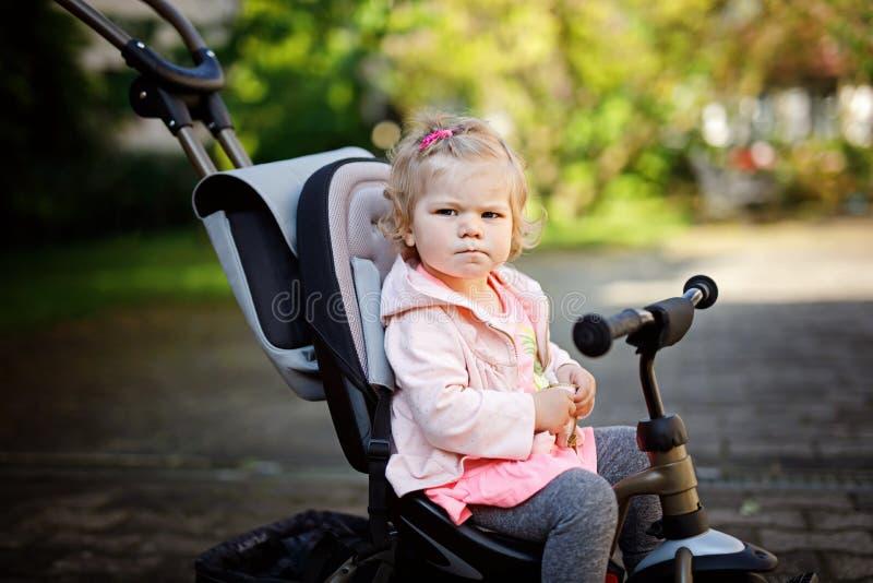 Gulligt förtjusande litet barnflickasammanträde på driftig bicyle eller trehjulingen Behandla som ett barn lite barnet som går fö arkivfoto