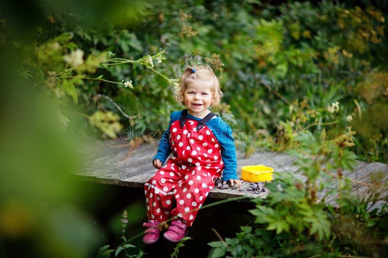 Gulligt förtjusande litet barnflickasammanträde på träbron och kasta små stenar in i en liten vik Roligt behandla som ett barn ha arkivbilder
