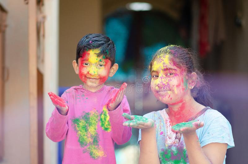 Gulligt förtjusande syskon som spelar med färger under holifestival av den indiska asiatiska caucasian idérika ståenden för färge fotografering för bildbyråer