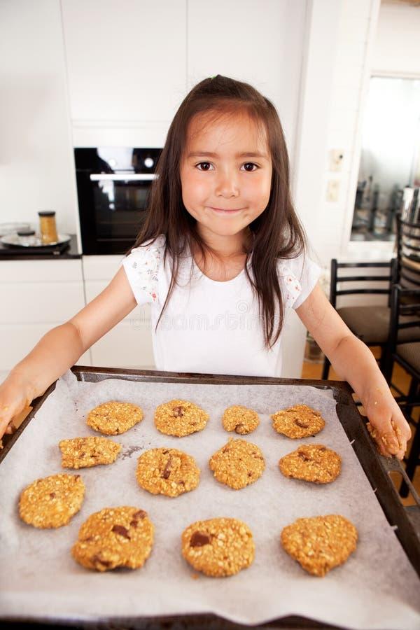 gulligt flickabarn för stekheta kakor arkivfoto