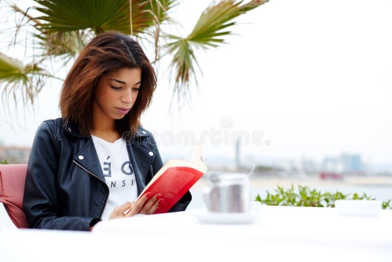 Gulligt flickasammanträde i ett kafé på stranden och att läsa en bok royaltyfria bilder