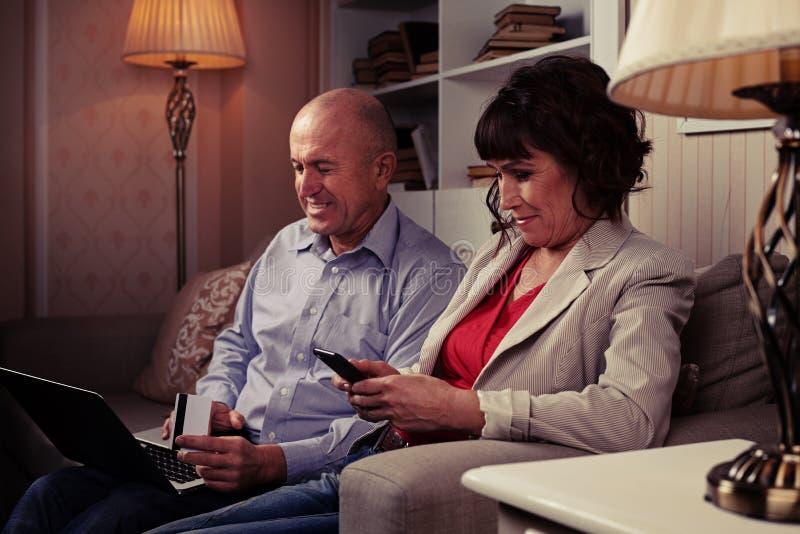 Gulligt folk som sitter på soffan och le royaltyfri fotografi
