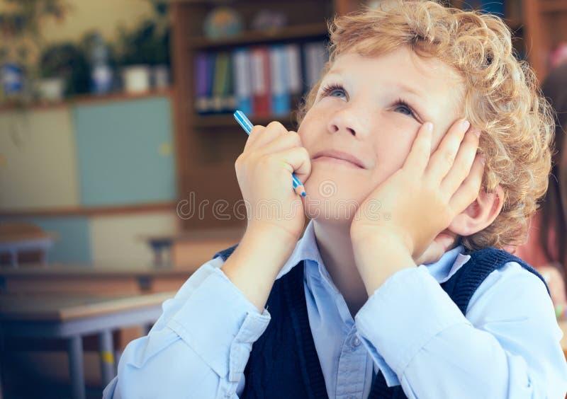 Gulligt fundersamt skolpojkesammanträde på skrivbordet och drömma arkivbilder
