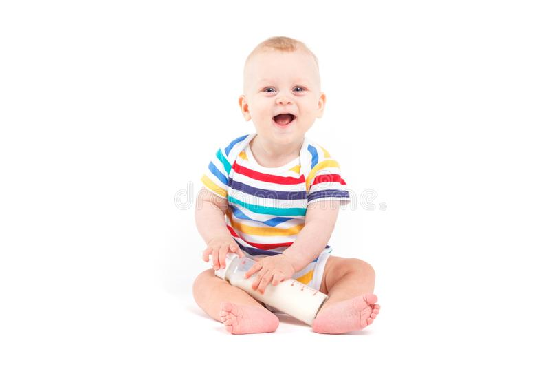 Gulligt glat behandla som ett barn pojken i färgrik skjortahåll mjölkar flaskan fotografering för bildbyråer