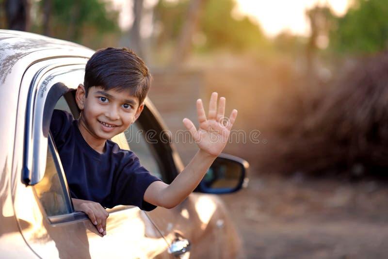 Gulligt indiskt barn som vinkar från bilfönster royaltyfri foto