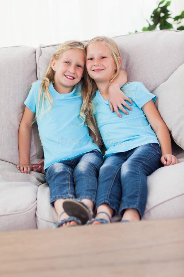 Gulligt kopplar samman sammanträde på en soffa royaltyfria foton