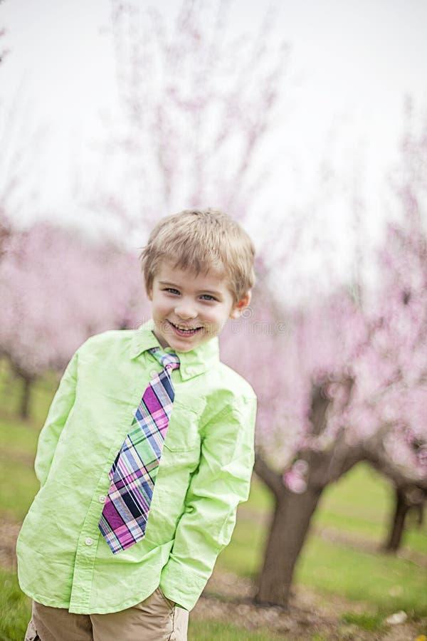 Gulligt le bärande band för pojke i vår arkivfoto