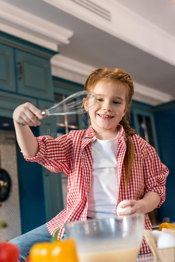 gulligt le barn som rymmer för att vifta, medan laga mat royaltyfri bild