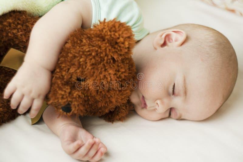 Gulligt lite att behandla som ett barn att sova i en söt sömn som kramar en björn arkivfoto