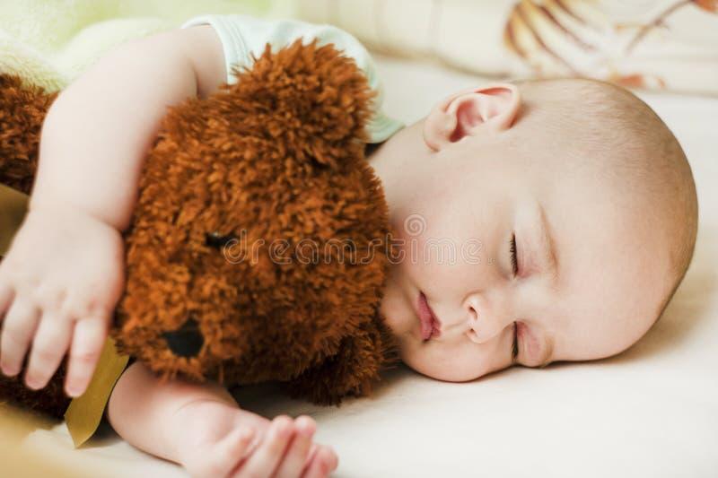 Gulligt lite att behandla som ett barn att sova i en söt sömn som kramar en björn arkivfoton