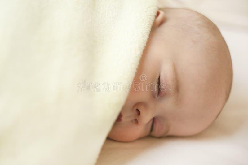 Gulligt lite att behandla som ett barn att sova i en söt sömn som kramar en björn royaltyfria foton