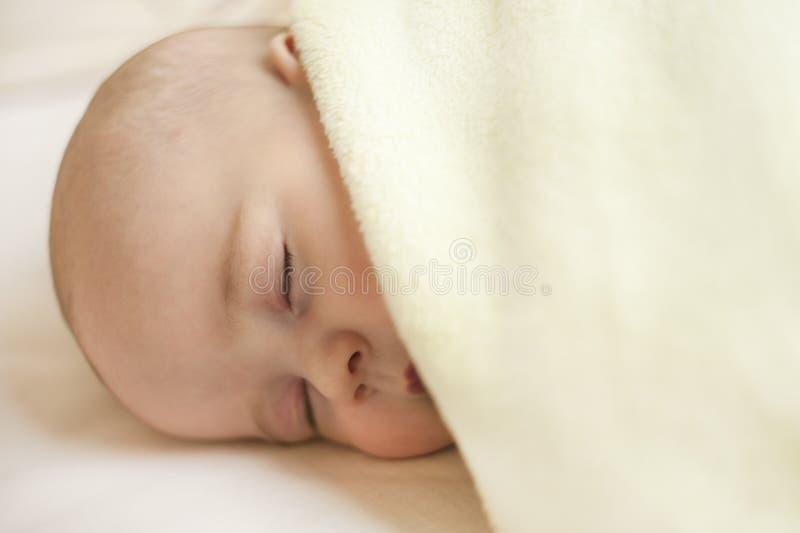Gulligt lite att behandla som ett barn att sova i en söt sömn som kramar en björn royaltyfria bilder
