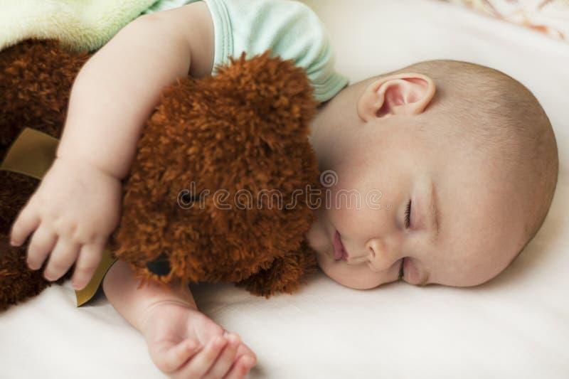 Gulligt lite att behandla som ett barn att sova i en söt sömn som kramar en björn fotografering för bildbyråer