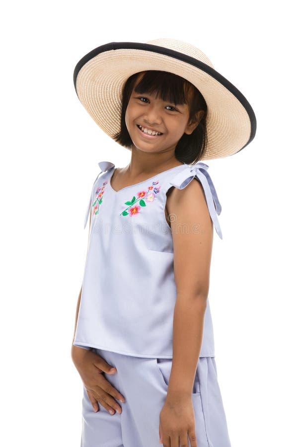 Gulligt liten flickaanseende, i att simma kläder och hatten på vit bakgrund arkivfoto